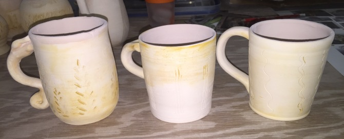 Pig Iron Glaze on three pottery mugs ready to be wood-fired.