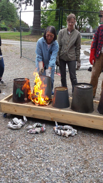 Raku firing - covering the pottery pieces in sawdust and paper and a can.